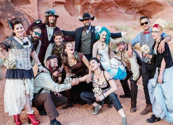 Group photo of steampunk bride and groom and wedding guests posing in the desert