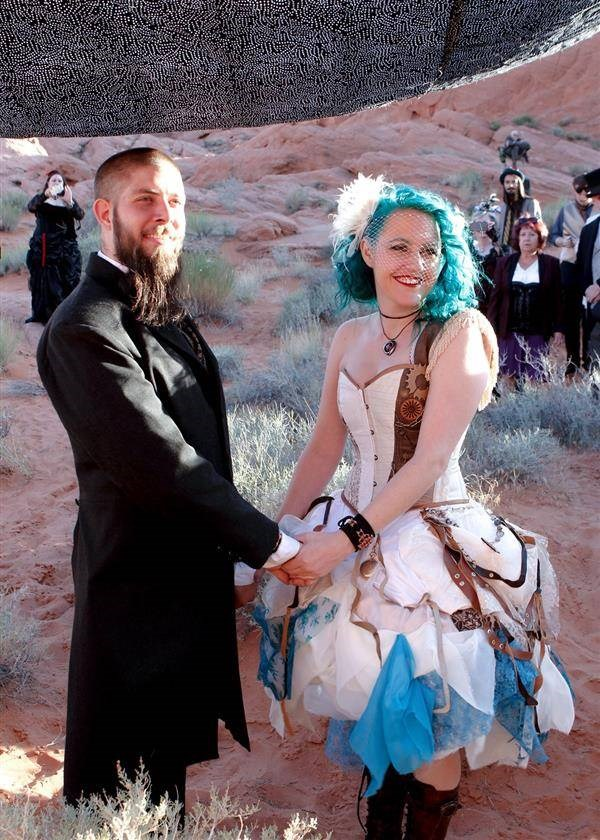Bearded groom and steampunk bride holding hands while taking wedding vows