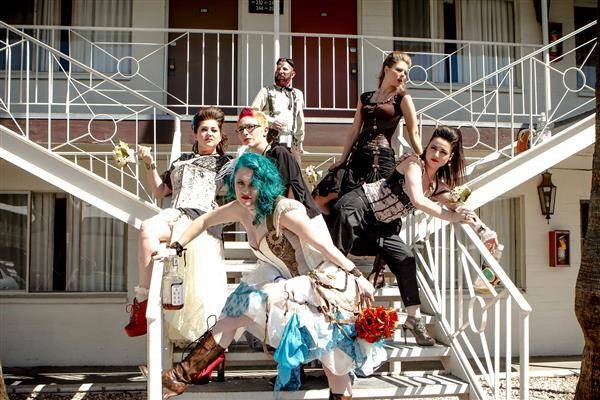 Steampunk bride, bridesmaids and guests posing outside motel