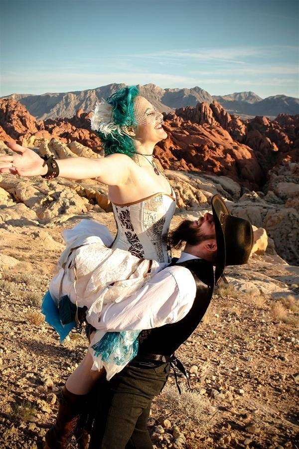 Steampunk groom lifting blue haired bride in the desert sunshine