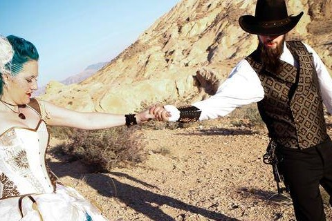 Newly married couple walking across the desert holding hands