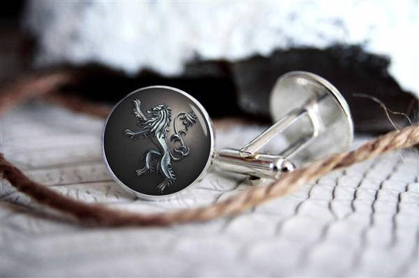 Silver cufflinks with house of Lannister sigil, lying on a table