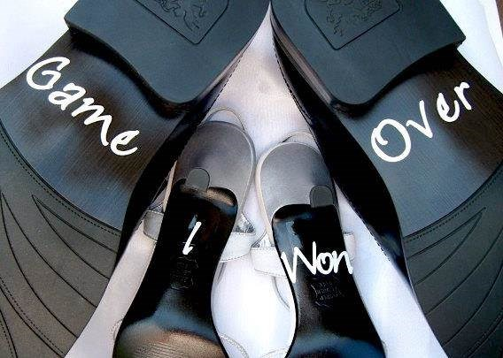 Soles of shoes with Game Over and I Won written on them.