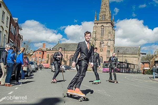 Groom and his groomsmen skateboarding through Hereford to his wedding