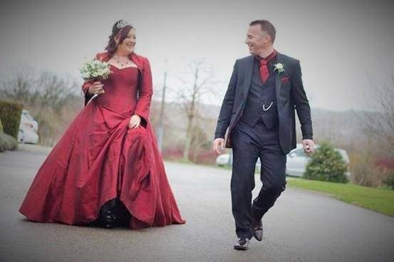 Bride in red wedding dress from Uptight Clothing with colour coordinated groom.