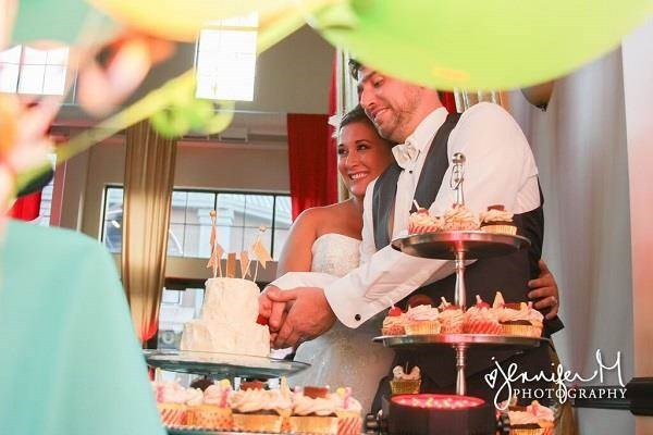 Bride & groom cutting the cake at their carnival themed wedding