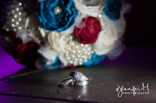 Wedding rings with bridal bouquet in the background