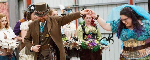 Steampunk bride and groom, with bridesmaids watching on.