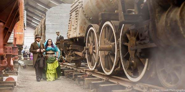 Steampunk bride and groom alongside locomotive train
