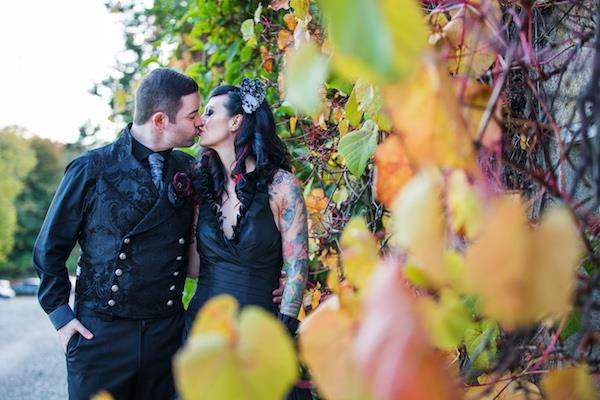 Gothic bride and groom kiss after their Halloween wedding