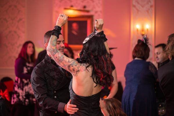 Tattooed bride dancing with her new husband
