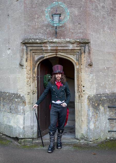 Groom in full Gothic attire at a castle wedding.
