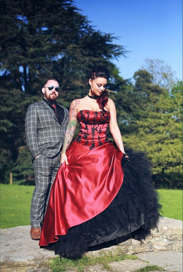The groom wearing tartan and the bride in red and black at their alternative wedding