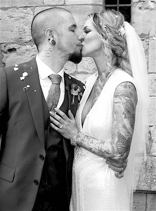 Tattooed bride and groom stealing a kiss.
